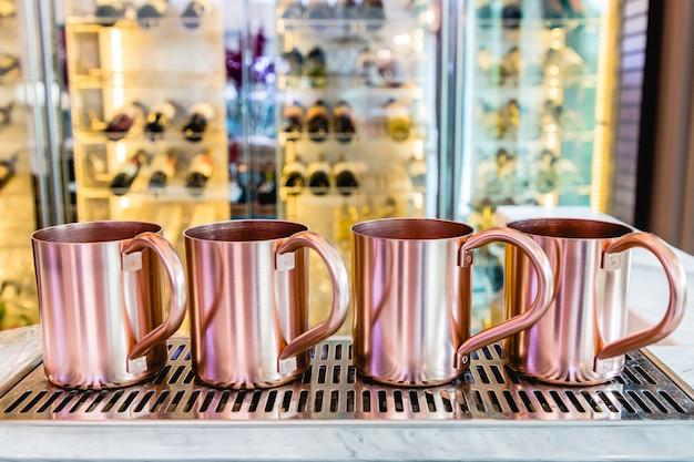 Copa de acero inoxidable de cobre o de oro rosa en una bandeja de acero inoxidable. wine bar borroso.