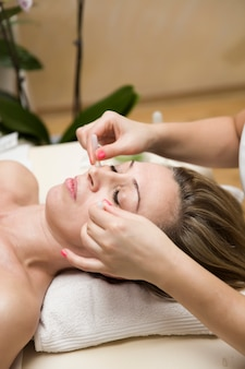 Copa aplicada a la piel facial de una paciente como parte del método tradicional de terapia de ventosas.