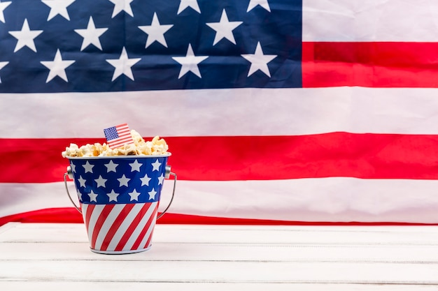 Copa con bandera americana y palomitas crujientes.