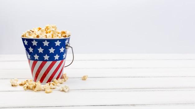 Copa con bandera americana y palomitas de maíz en superficie blanca