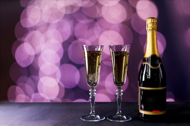 Copa de champagne con botella y efecto bokeh.