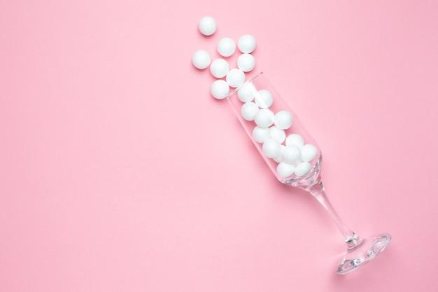 Copa de champán con bolas blancas en estilo minimalista rosa.