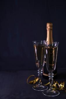 Copa de champán y botella con serpentinas sobre fondo negro