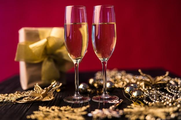 Copa de champán con cajas de regalo y adornos navideños. presente para uno especial.