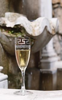 Copa de champán y fuente en el fondo.