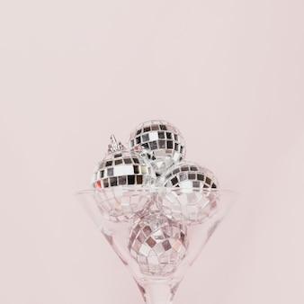 Copa de champán transparente con bolas de discoteca.
