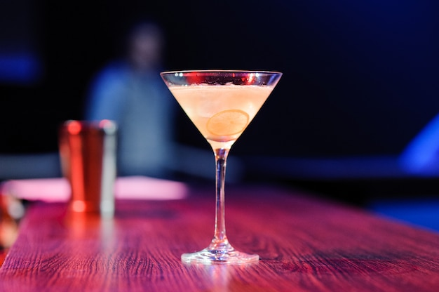 Copa de cóctel alcohólico con rodaja de limón
