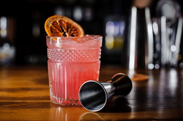 Copa de cóctel alcohólico rosa decorado con una rodaja de naranja