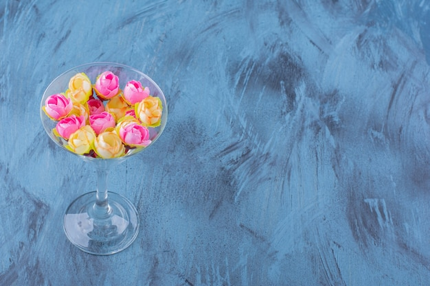 Copa de cóctel con arreglo de flores de colores en azul.