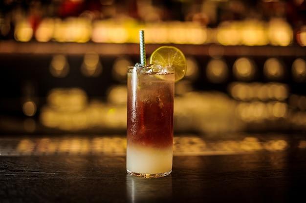 Copa de cóctel con bebida fría agridulce fresca decorada con paja y rodaja de limón