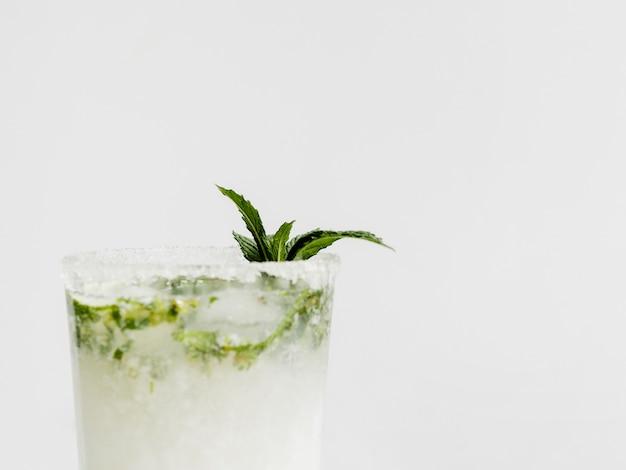 Copa de coctel blanco con menta y borde azucarado.