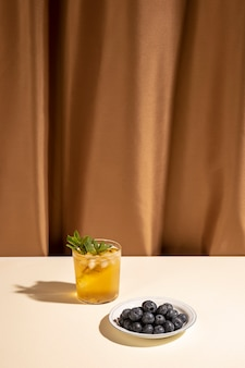 Copa de cóctel casero con arándanos en placa sobre mesa blanca cerca de cortina marrón