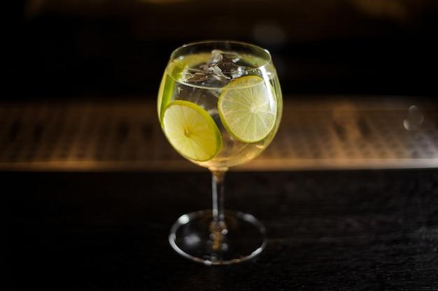 Copa de cóctel grande y elegante con cóctel de cítricos agrios y dulces frescos con rodajas de lima