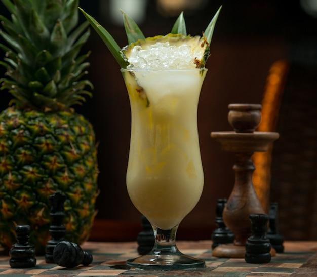 Copa de cóctel helado de piña en un tablero de ajedrez