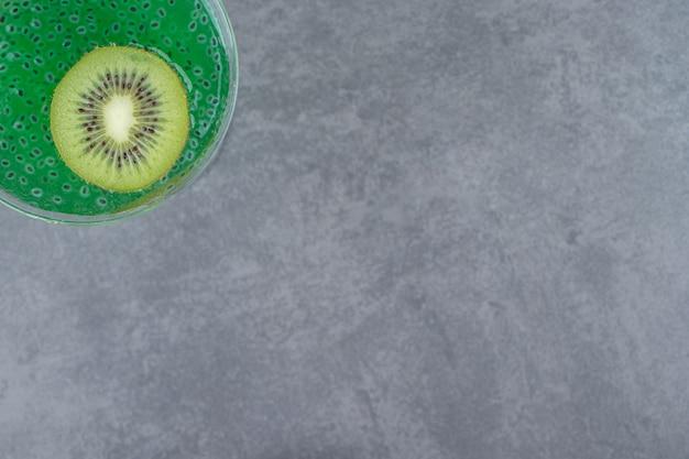 Una copa de cóctel de jugo de kiwi con una rodaja de fruta. foto de alta calidad