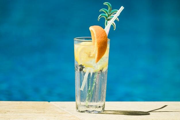 Copa de cóctel con limón y rodajas de naranja y pajitas