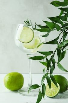Copa de cóctel con limón sobre mesa de madera blanca