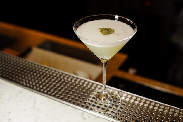 Copa de cóctel llena de bebida alcohólica fresca decorada con hojas de abedul