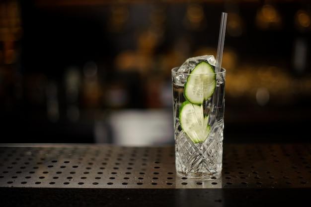 Copa de cóctel llena de bebida alcohólica fresca con rodajas de pepino y ginebra
