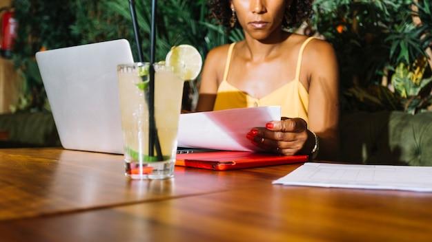 Copa de cóctel en la mesa frente a una mujer joven examinando el documento en el restaurante