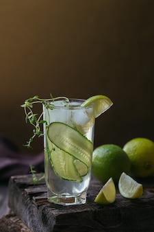 Copa de cóctel de pepino o cóctel sin alcohol, refrescante bebida de verano con hielo picado y agua con gas sobre una superficie de madera