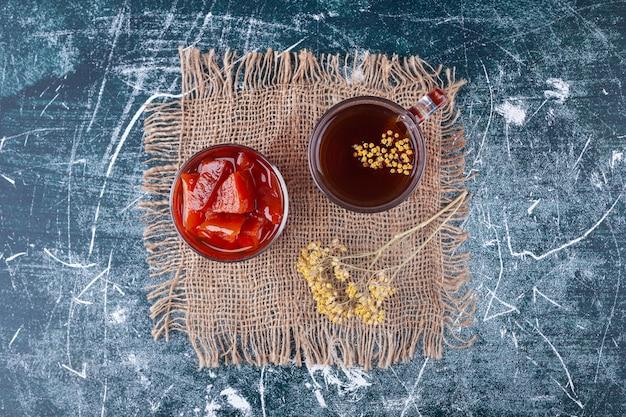 Copa de cóctel rojo con rodajas de frutas sobre la superficie de mármol.