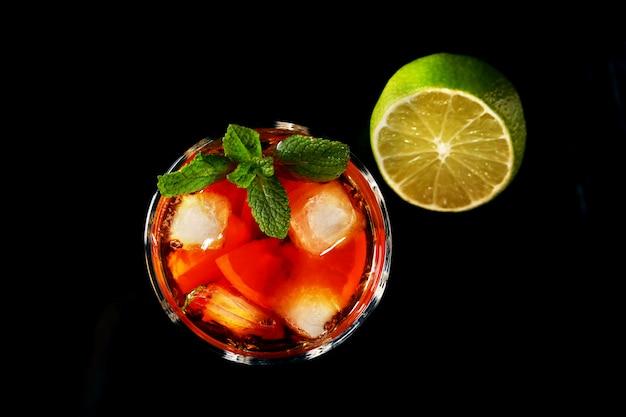 Copa de cóctel de ron oscuro con limón, naranja, cubitos de hielo y hojas de menta.