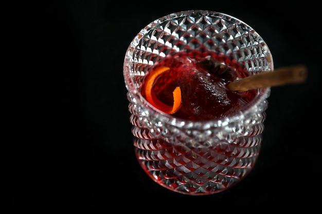 Copa de cóctel rosa con hielo en una barra de bar