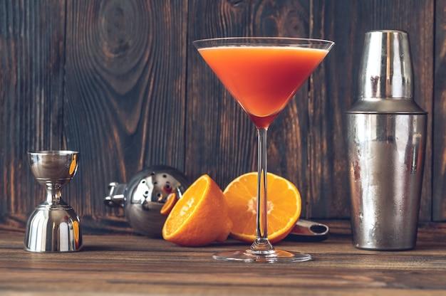 Copa de cóctel de sangre y arena en copa de martini adornado con piel de naranja