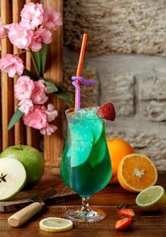 Copa de cóctel verde con rodajas de manzana, hielo y fresa.