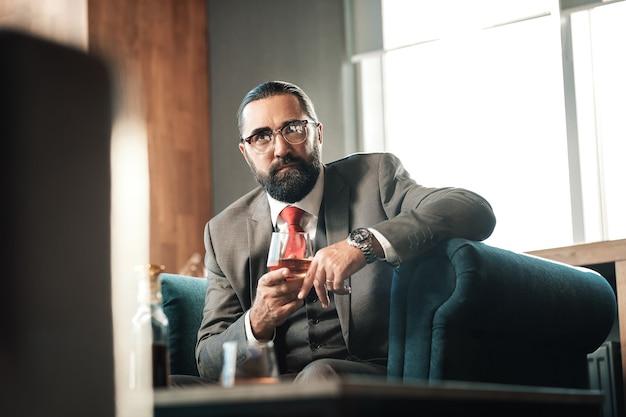 Copa de coñac. abogado maduro barbudo de pelo oscuro con gafas bebiendo copa de coñac