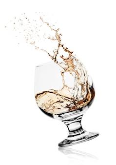 Copa de coñac elegante con bebida que salpica