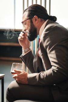 Copa de coñac. empresario maduro barbudo vistiendo corbata roja sosteniendo una copa de coñac en su mano
