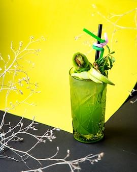 Copa de cristal de cóctel verde con rodaja de manzana verde y kiwi