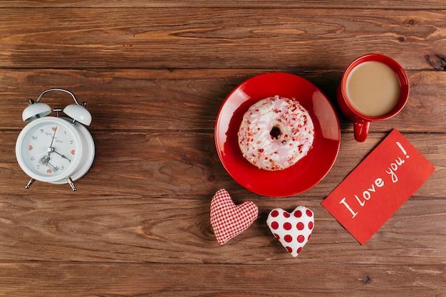 Copa y donut en plato entre las decoraciones de san valentín.