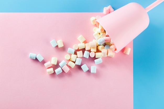Copa llena de malvaviscos en superficie de papel rosa