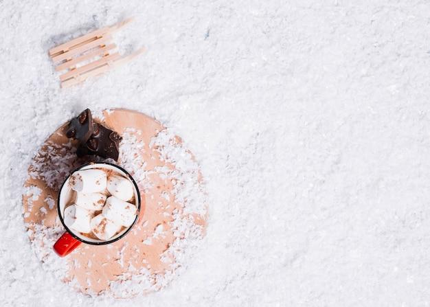 Copa con malvaviscos cerca de chocolate en el stand y jumper de juguete entre la nieve