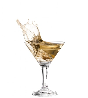 Una copa de martini sobre un fondo blanco; el agua se agita y salpica mientras una aceituna verde española con pimiento cae en el vaso; formato horizontal