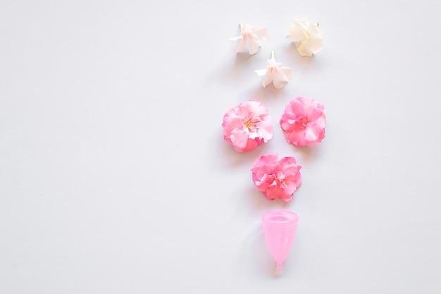Copa menstrual y flores sobre fondo claro.