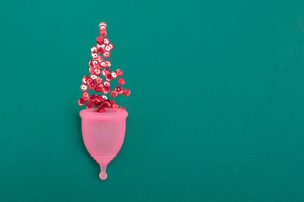Copa menstrual rosa con destellos rojos sobre fondo verde