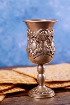 Copa de plata judía con vino con matzos concepto de pascua.