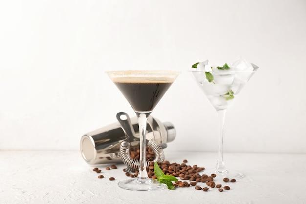 Copa de sabroso cóctel de martini espresso y coctelera sobre fondo claro