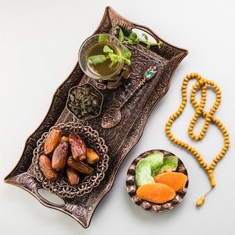 Copa de té con dátiles frutales y abalorios en bandeja.