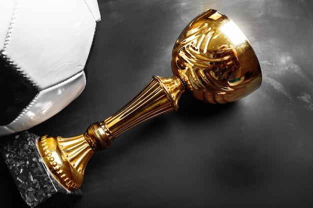 Copa de trofeos y balón de fútbol.