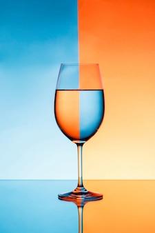 Copa de vino con agua sobre fondo azul y naranja.