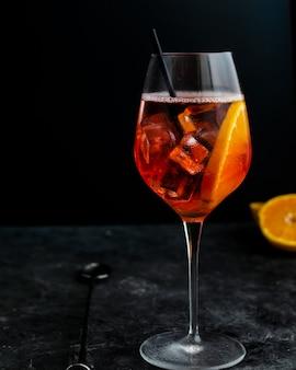 Copa de vino con aperol spritz, cóctel alcohólico italiano en la oscuridad