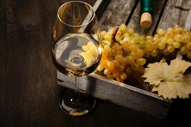 Copa de vino blanco, una botella y uvas sobre la mesa.