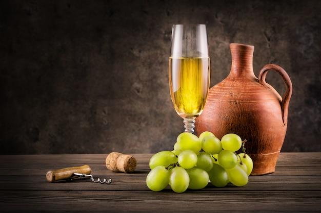 Copa de vino blanco, jarra y uvas