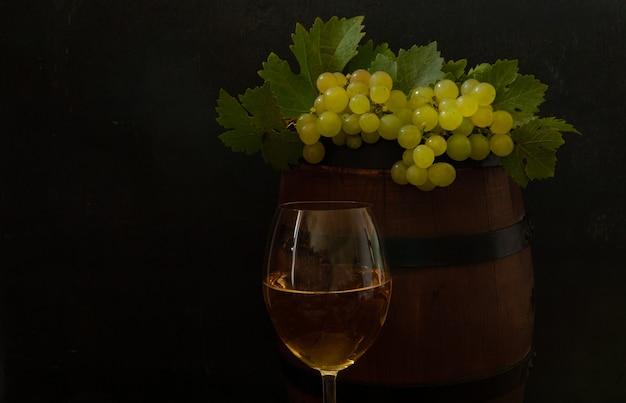Una copa de vino blanco, un racimo de uvas con hojas y un barril de vino.