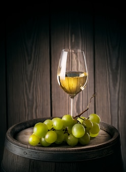 Copa de vino blanco con racimo de uvas maduras
